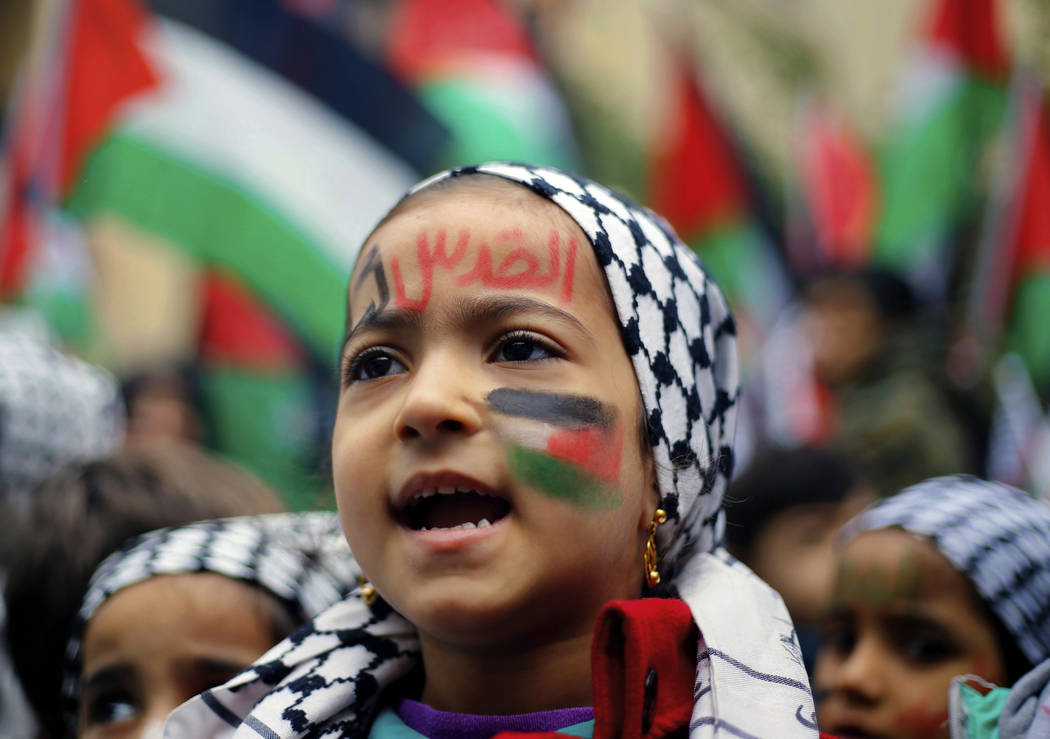 "A girl with a Palestinian flag and Arabic that read ""Jerusalem is for us"" painted on her face chants slogans during a sit-in in the Bourj al-Barajneh Palestinian refugee camp in  ..."