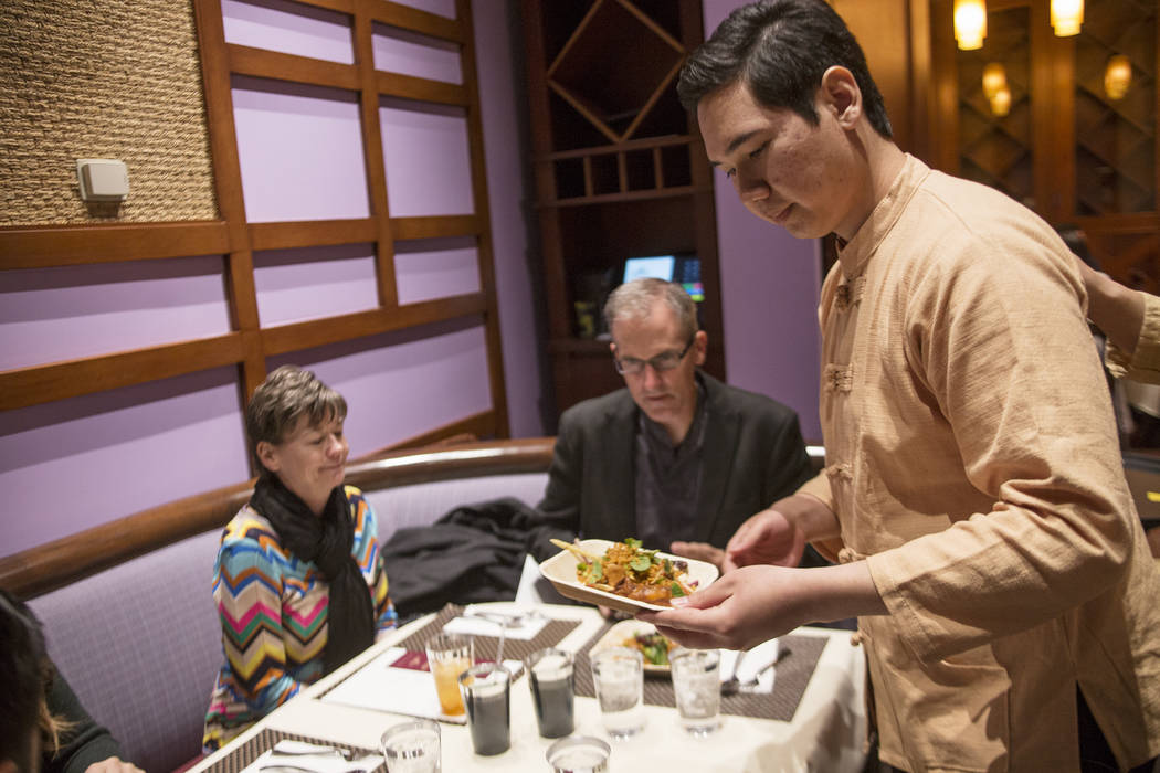 Server Bank Narongchai sets food off at a table at the new second location of Lotus of Siam, a thai restaurant, in Las Vegas, Sunday, Dec. 10, 2017. The restaurant held a birthday party for Chef S ...