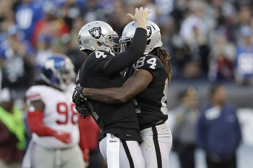 Oakland Raiders quarterback Derek Carr (4) hugs wide receiver Cordarrelle Patterson (84) during the second half of an NFL football game against the New York Giants in Oakland, Calif., Sunday, Dec. ...