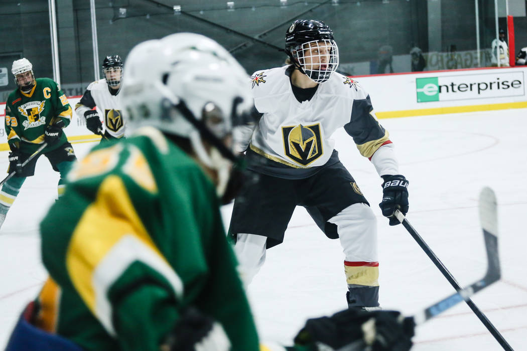 Vegas Jr. Golden Knights' Robert Purdy (5), right, eyes the puck during the third period of a hockey game against the Edison Chargers at City National Arena in Las Vegas, Friday, Dec. 8, 2017. Edi ...