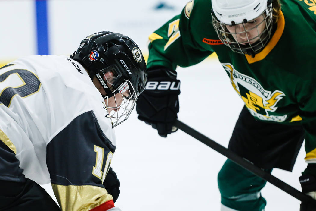 Vegas Jr. Golden Knights' Antonio Buck (10), left, and  Edison Chargers' James McGuire (24), right, battle over the puck during the third period of a hockey game at City National Arena in Las Vega ...