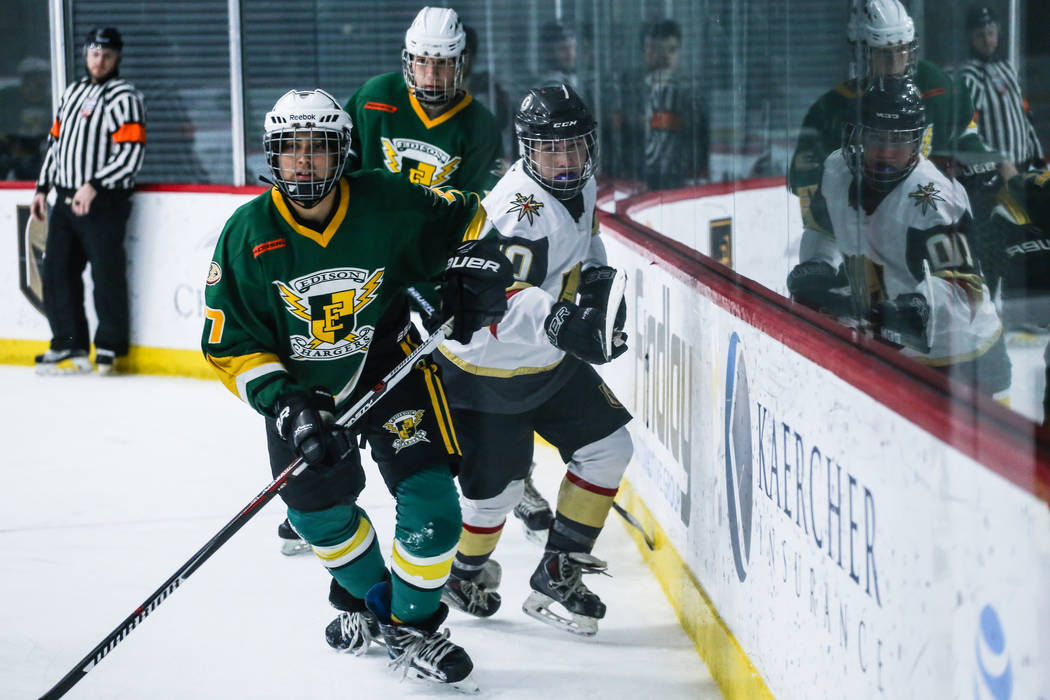 Edison Chargers' Patrick Jackson (77), left, and Vegas Jr. Golden Knights' Antonio Buck (10), right, chase after the puck during the third period of a hockey game at City National Arena in Las Veg ...
