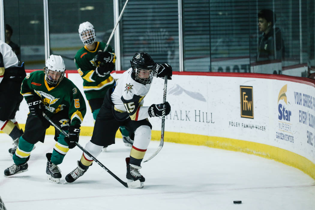 Edison Chargers' Stephen Bedard (6), left, and Vegas Jr. Golden Knights' Jo Heinzelman (15), right, chase after the puck during the third period of a hockey game at City National Arena in Las Vega ...