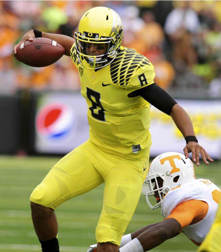 FILE - In this Sept. 14, 2013, file photo, Oregon quarterback Marcus Mariota (8) runs for some yardage during the first quarter of the NCAA college football game Tennessee in Eugene, Ore. (AP Phot ...