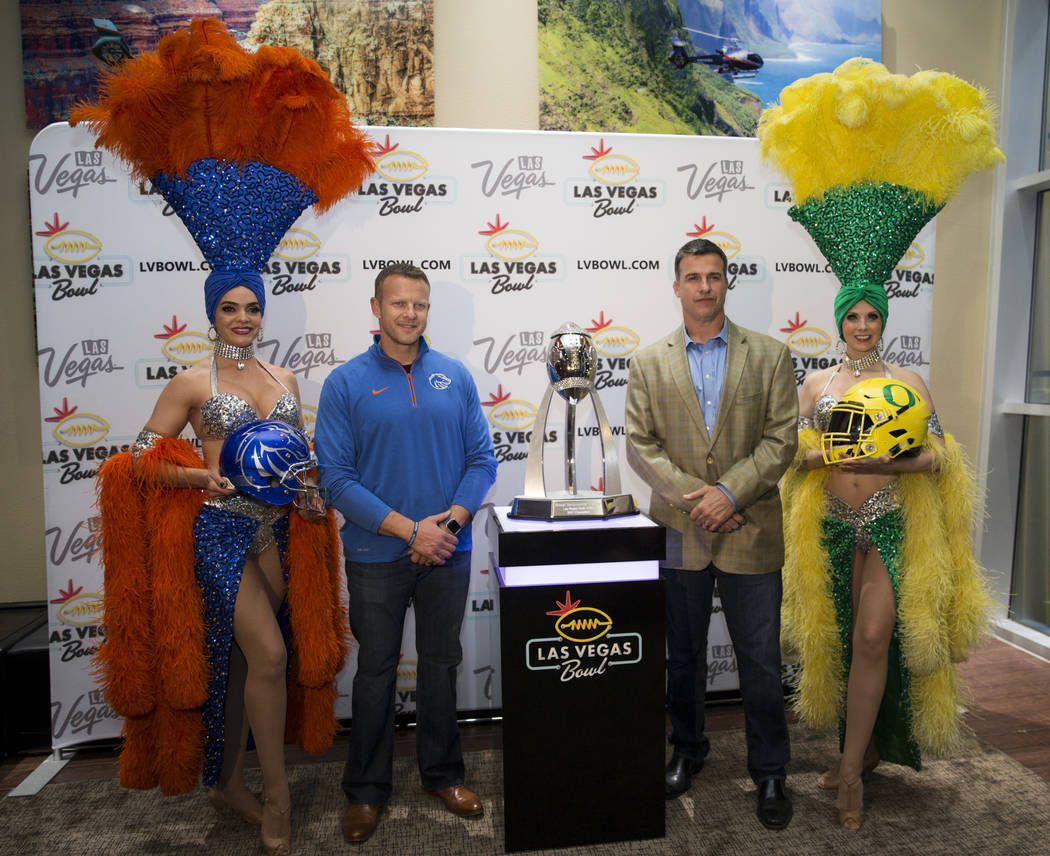 Boise State football head coach Bryan Harsin, left, and Oregon football head coach Mario Cristobal pose with Las Vegas showgirls during a press conference in advance of the Las Vegas Bowl game, at ...