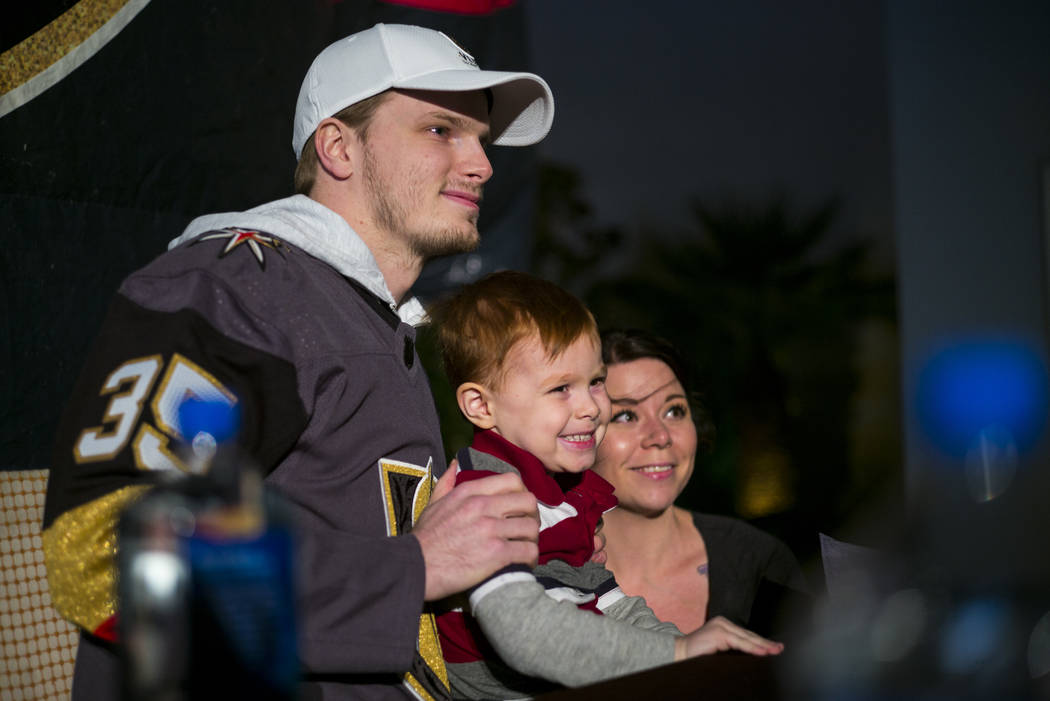 "Golden Knights' Oscar Dansk poses for a photo with 4-year-old River Ercanbrack and his mother, Sarah Pick, during the ""Night With the Golden Knights"" event at the ice rink at The ..."