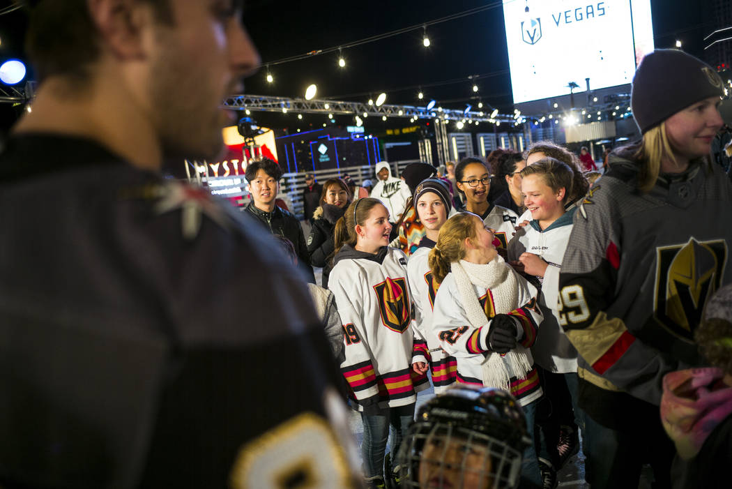 "Golden Knights' Alex Tuch, left, greets young hockey fans during the ""Night With the Golden Knights"" event at the ice rink at The Cosmopolitan of Las Vegas in Las Vegas on Wednes ..."