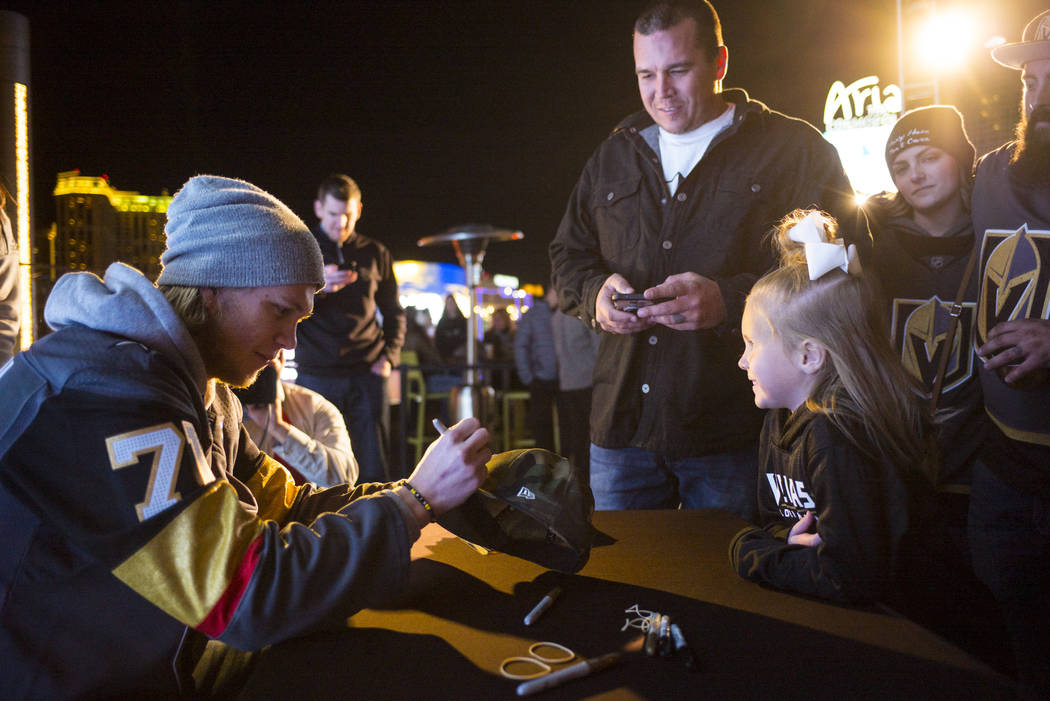 "Golden Knights' William Karlsson, left, signs an autograph for 5-year-old Stella Wyson during the ""Night With the Golden Knights"" event at the ice rink at The Cosmopolitan of Las ..."