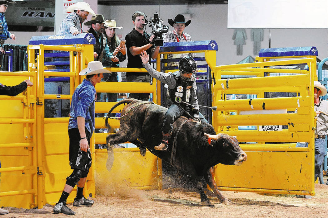 A young cowboy shows his form out of the chute in bull riding during the 2016 Junior National Finals Rodeo at the Cowboy Christmas Wrangler Rodeo Arena in the Las Vegas Convention Center's South H ...