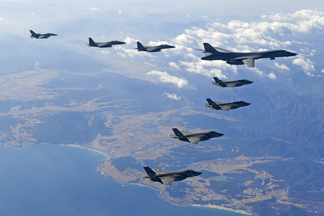 In this photo provided by South Korea Defense Ministry, U.S. Air Force B-1B bomber, right top, flies over the Korean Peninsula with South Korean fighter jets and U.S. fighter jets during the combi ...