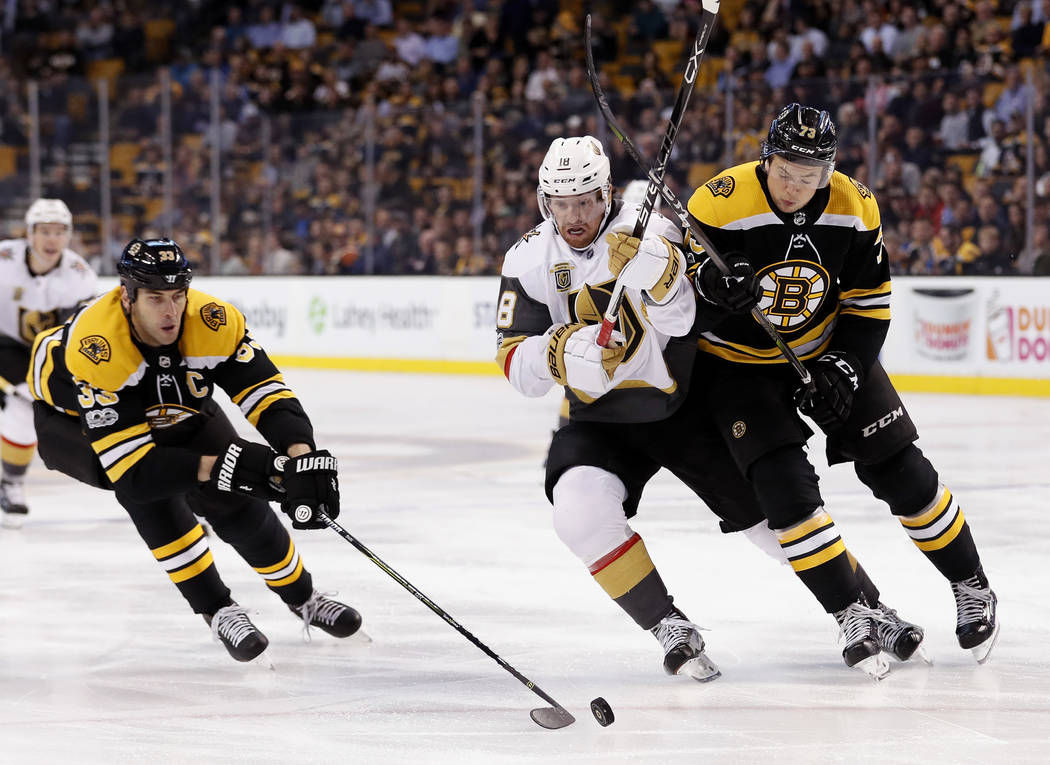 Boston Bruins defenseman Zdeno Chara reaches in for the puck as teammate Charlie McAvoy, right, battles Vegas Golden Knights' James Neal during the first period of an NHL hockey game in Boston, Th ...