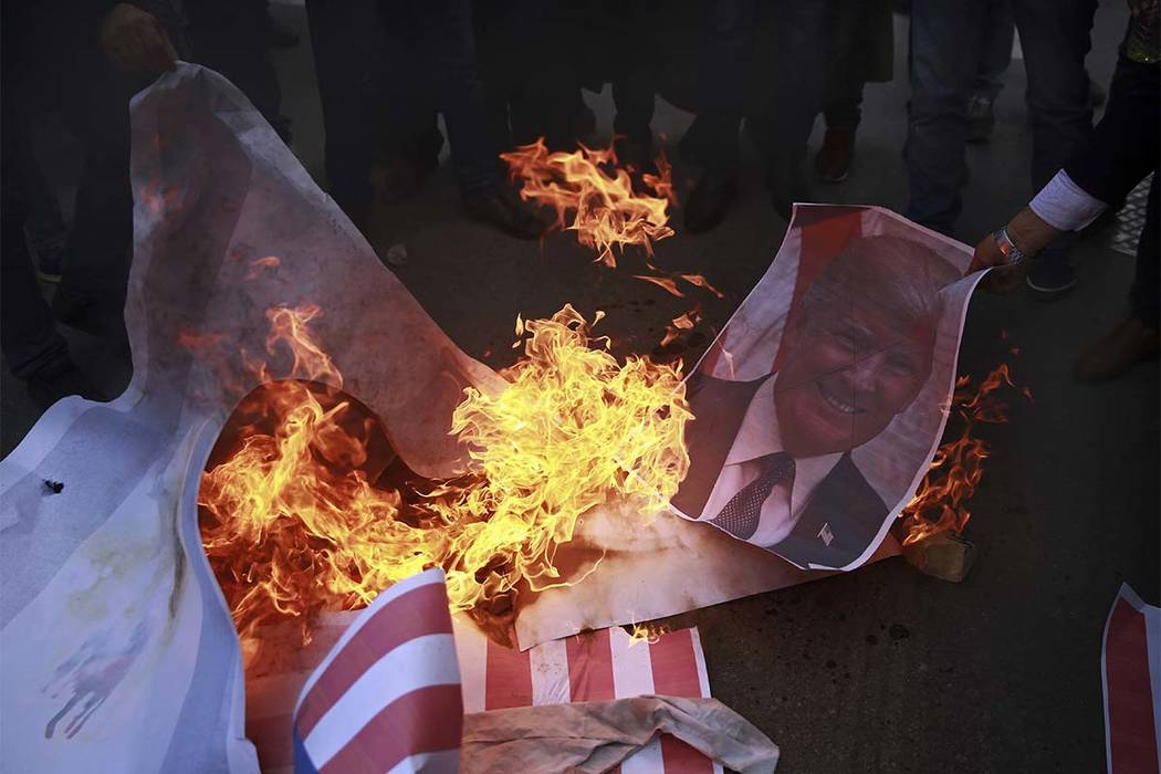 Palestinians burn a poster of President Donald Trump and a representation of an American flag, during a protest against the U.S. decision to recognize Jerusalem as Israel's capital, in Gaza City T ...