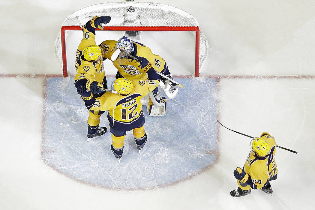 Nashville Predators goalie Pekka Rinne (35), of Finland, celebrates with Filip Forsberg (9), of Sweden, Mike Fisher (12), and Roman Josi (59), of Switzerland, after the Predators beat the Anaheim  ...