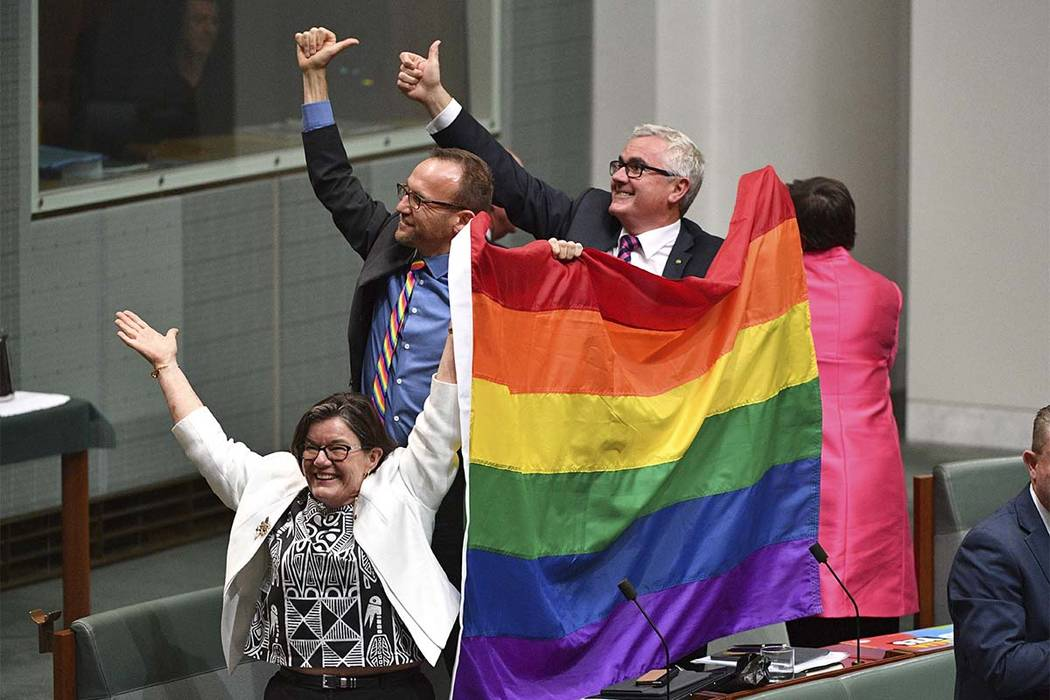 Members of parliament from left Cathy McGowan Adam Brandt and Andrew Wilkie celebrate the passing of the Marriage Amendment Bill in the House of Representatives at Parliament House in Canberra