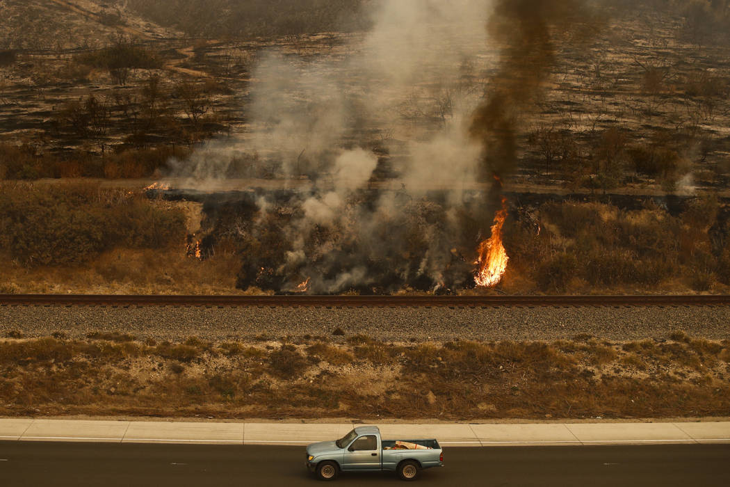 A pickup truck passes a wildfire burning along the 101 Freeway in Ventura, Calif., Thursday, Dec. 7, 2017. The wind-swept blazes have forced tens of thousands of evacuations and destroyed dozens o ...