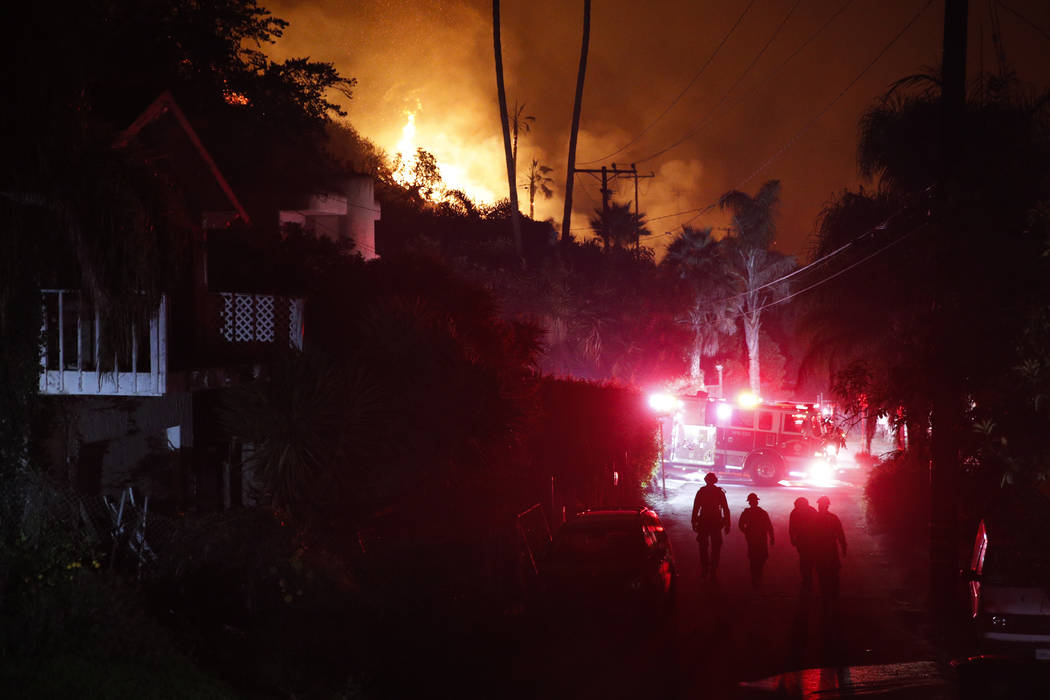 Firefighters walk along an alley as a wildfire burns along a hillside toward homes in La Conchita, Calif., Thursday, Dec. 7, 2017. The wind-swept blazes have forced tens of thousands of evacuation ...