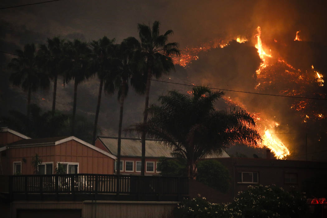 A wildfire threatens homes as it burns along a hillside in La Conchita, Calif., Thursday, Dec. 7, 2017. The wind-swept blazes have forced tens of thousands of evacuations and destroyed dozens of h ...