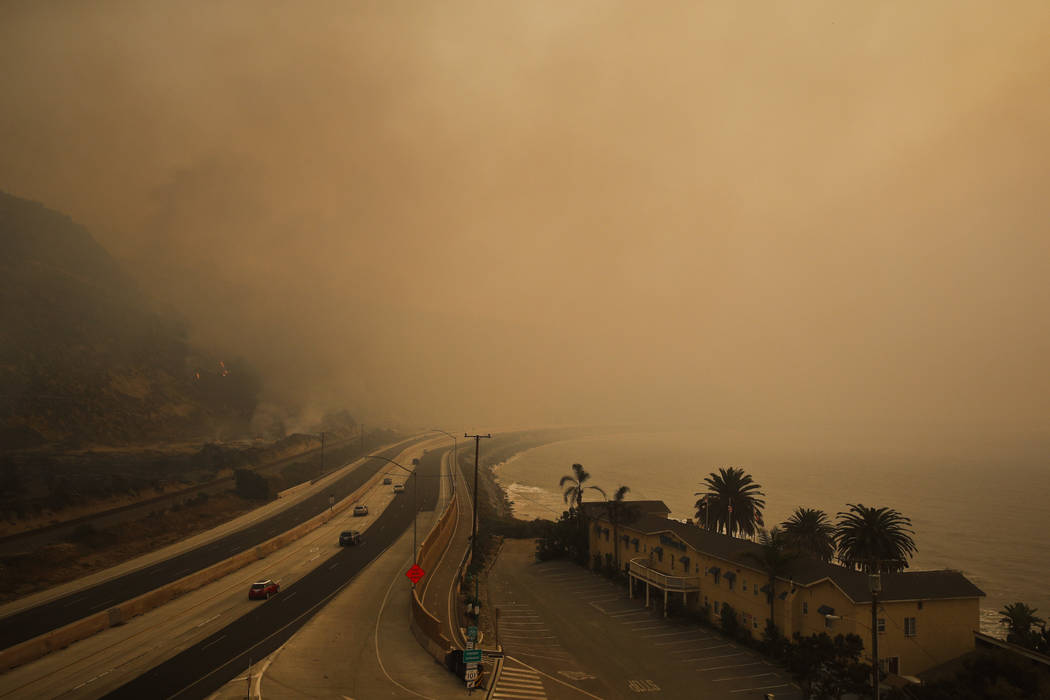 Traffic moves along the 101 Freeway as smoke from a wildfire fills the air in Ventura, Calif., Thursday, Dec. 7, 2017. The wind-swept blazes have forced tens of thousands of evacuations and destro ...