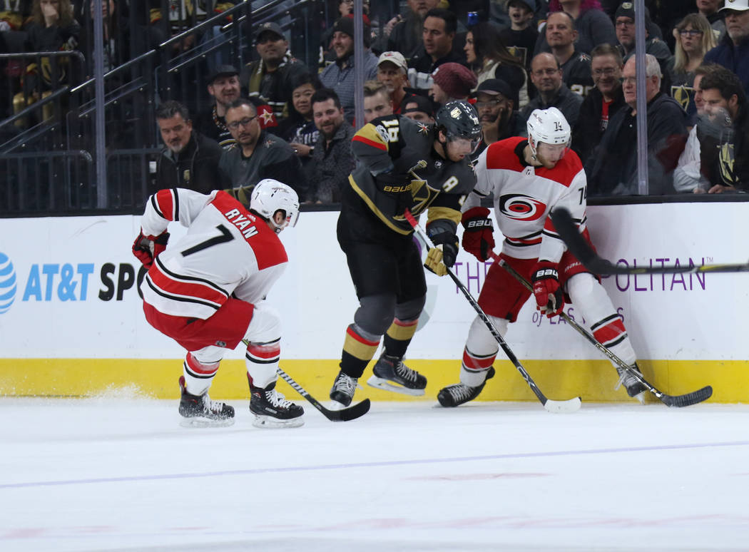 Vegas Golden Knights left wing James Neal (18) works to take the puck away from Carolina Hurricanes defenseman Jaccob Slavin (74) as center Derek Ryan (7) skates towards the action during the firs ...
