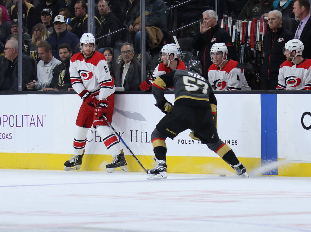 Vegas Golden Knights left wing David Perron (57) handles the puck as Carolina Hurricanes defenseman Noah Hanifin (5) tries to defend during the first period of a NHL game in Las Vegas, Tuesday, De ...
