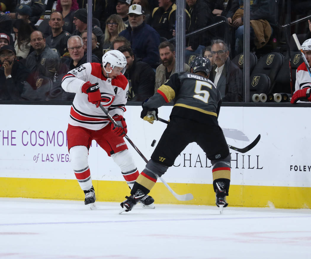 Carolina Hurricanes left wing Jeff Skinner (53) and Vegas Golden Knights defenseman Deryk Engelland (5) fight for possession during the first period of a NHL game in Las Vegas, Tuesday, Dec. 12, 2 ...