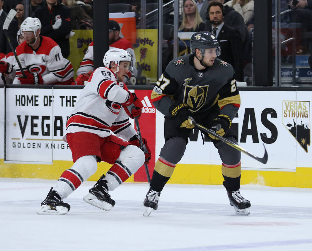 Carolina Hurricanes left wing Jeff Skinner (53) shoots the puck away from Vegas Golden Knights defenseman Shea Theodore (27) during the first period of a NHL game in Las Vegas, Tuesday, Dec. 12, 2 ...