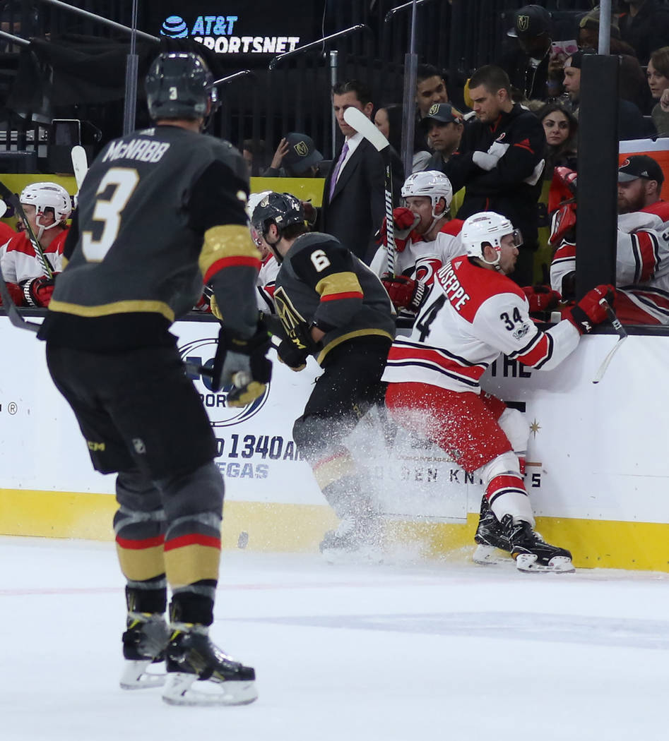 Carolina Hurricanes left wing Phillip Di Giuseppe (34) and Vegas Golden Knights defenseman Colin Miller (6) fight for the puck against the wall during the first period of a NHL game in Las Vegas,  ...