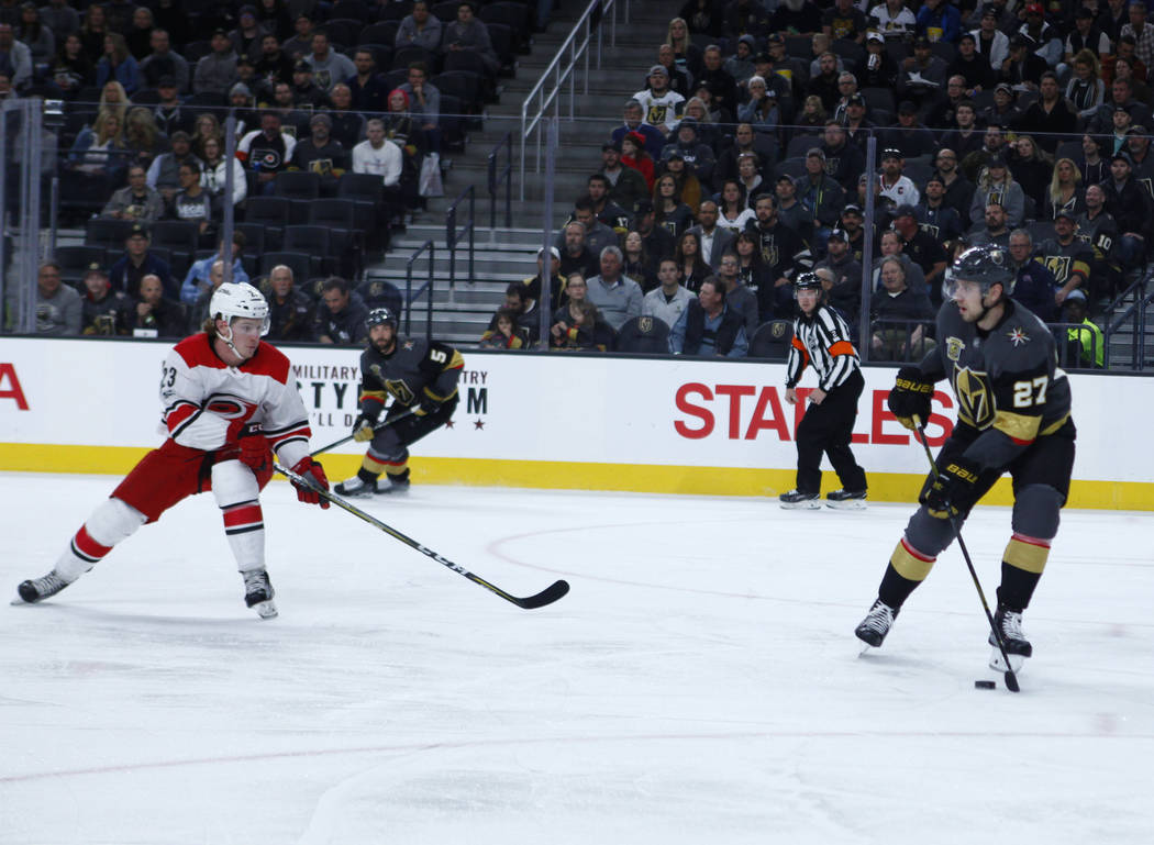 Vegas Golden Knights defenseman Shea Theodore (27) handles the puck as Carolina Hurricanes left wing Brock McGinn (23) prepares to defend during the first period of a NHL game in Las Vegas, Tuesda ...