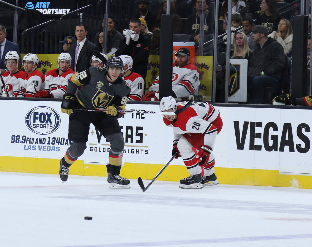 Vegas Golden Knights left wing Tomas Nosek (92) and Carolina Hurricanes right wing Sebastian Aho (20) skate towards the puck during the first period of a NHL game in Las Vegas, Tuesday, Dec. 12, 2 ...