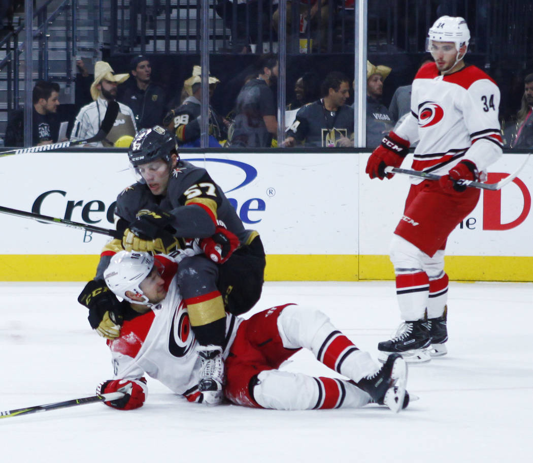 Vegas Golden Knights left wing David Perron (57) and Carolina Hurricanes center Marcus Kruger (16) engage in a tussle during the first period of a NHL game in Las Vegas, Tuesday, Dec. 12, 2017. He ...