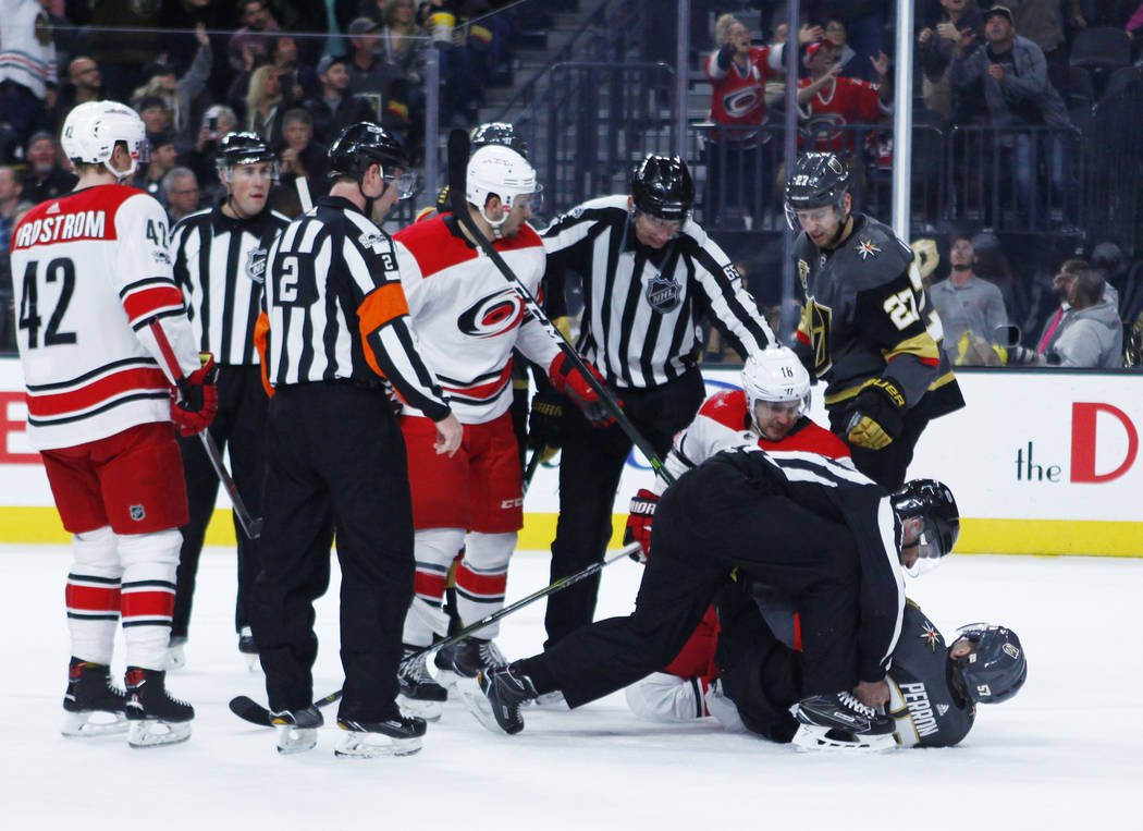 Referees break up a tussle between Vegas Golden Knights left wing David Perron (57) and Carolina Hurricanes center Marcus Kruger (16) during the first period of a NHL game in Las Vegas, Tuesday, D ...