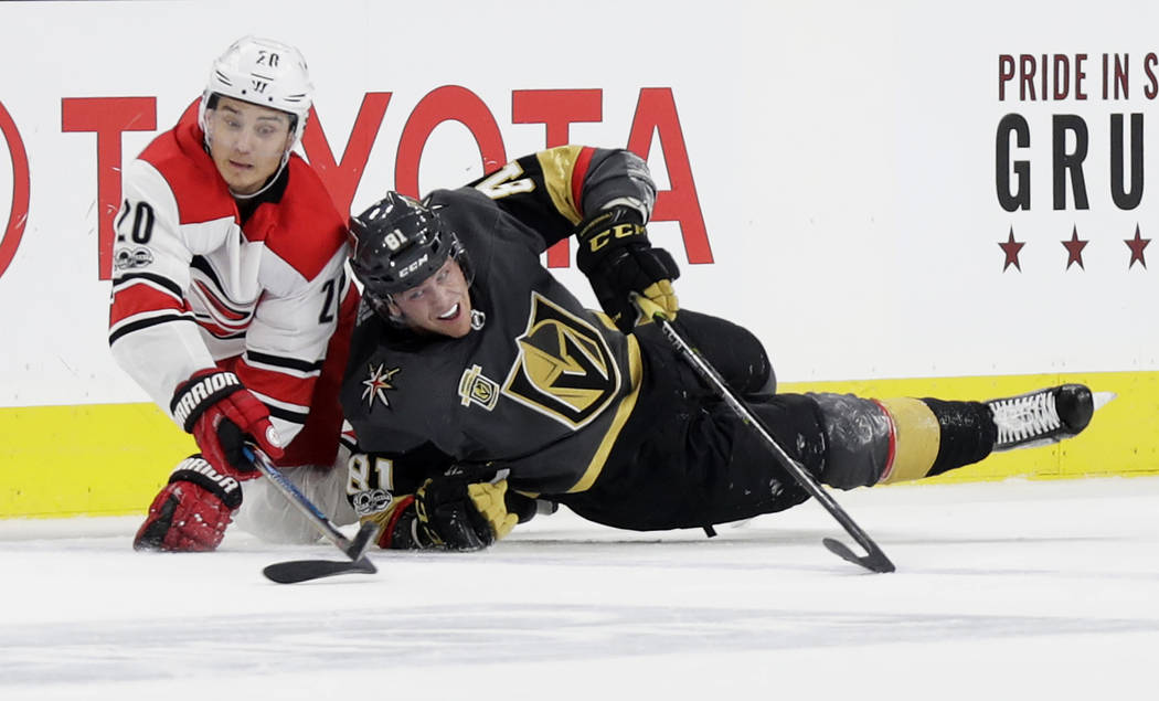 Carolina Hurricanes right wing Sebastian Aho (20) and Vegas Golden Knights center Jonathan Marchessault vies for a loose puck during the third period of an NHL hockey game Tuesday, Dec. 12, 2017,  ...