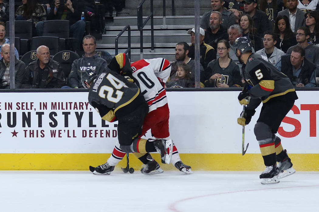 Vegas Golden Knights center Oscar Lindberg (24) and Carolina Hurricanes right wing Sebastian Aho (20) fight for the puck as defenseman Deryk Engelland (5) skates towards them during the first peri ...