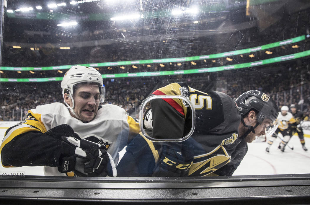 Penguins left wing Conor Sheary (43) fights for the puck with Golden Knights defenseman Jon Merrill (15) in the second period of Pittsburgh's road matchup with the Golden Knights on Thursday, Dec. ...