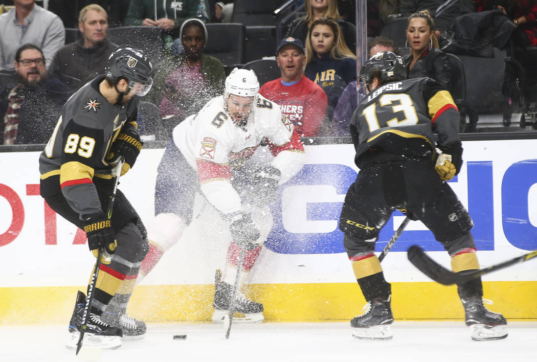 Golden Knights' Alex Tuch (89) and Brendan Leipsic (13) fight for the puck against Florida Panthers' Alexander Petrovic (6) during an NHL hockey game at T-Mobile Arena in Las Vegas on Sunday, Dec. ...