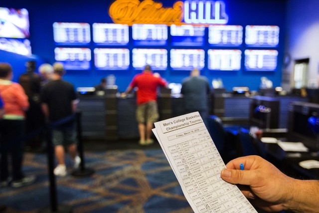 Wes Dorner from Green Bay, Wis., checks a parlay card for the NCAA Men's basketball in the  William Hill Race & Sports Book at the Plaza Hotel-Casino on Friday, March 18, 2016. (Jeff Scheid/La ...
