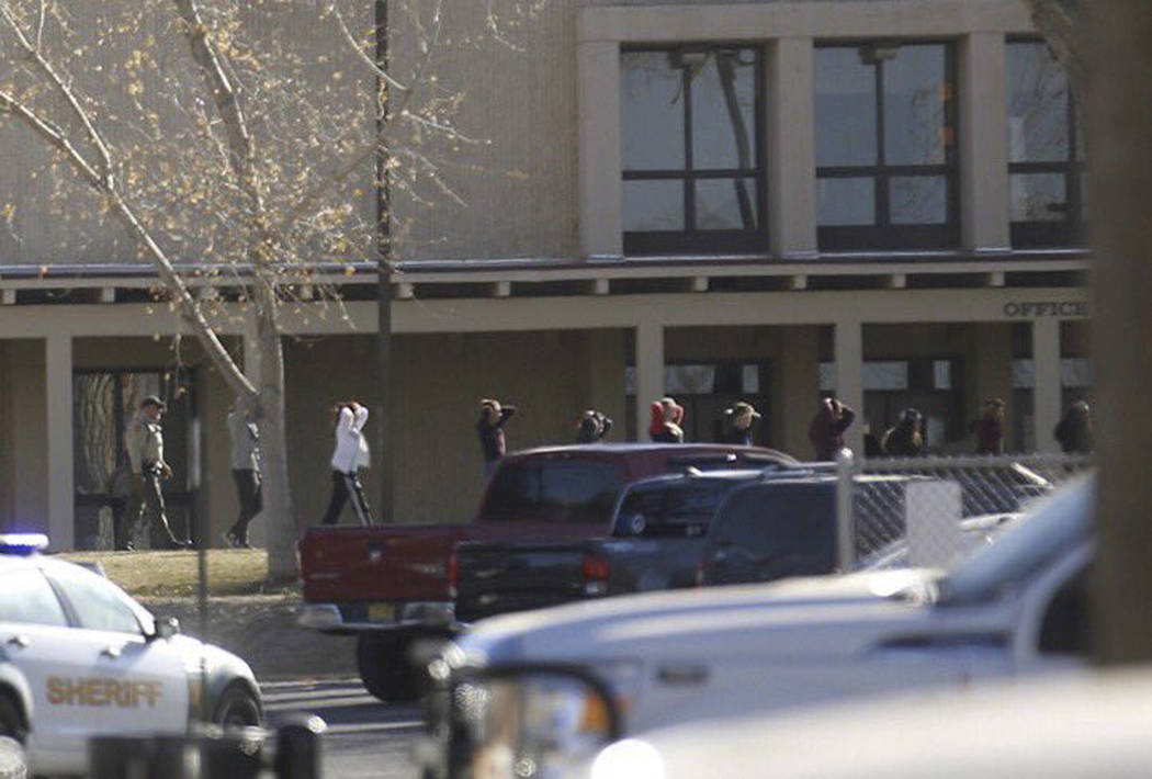 Students are led out of Aztec High School after a shooting Thursday, Dec. 7, 2017, in Aztec, N.M. The school is in the Four Corners region and is near the Navajo Nation. (Jon Austria /The Daily Ti ...