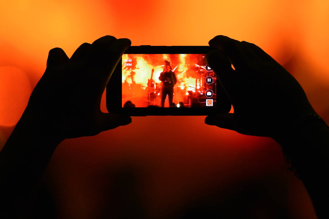 A fan records a performance by artist The Weeknd at the 2015 Billboard Hot 100 Music Festival at Nikon at Jones Beach Theater on Saturday, Aug. 22, 2015, in Wantagh, N.Y. (Photo by Scott Roth/Invi ...