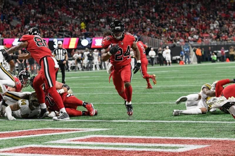 Dec 7, 2017; Atlanta, GA, USA; Atlanta Falcons running back Devonta Freeman (24) scores a touchdown against the New Orleans Saints during the first half at Mercedes-Benz Stadium. Mandatory Credit: ...