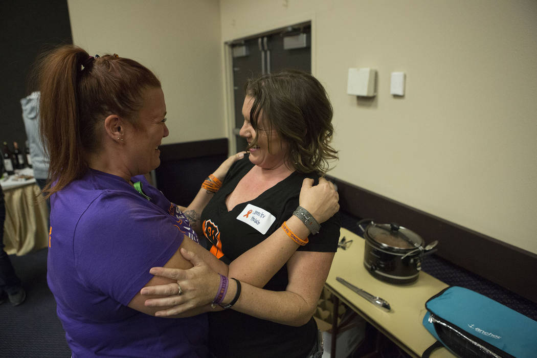 Heather Goose, left, and Jennifer Holub embrace after meeting for the first time in real life during a Thanksgiving dinner for Route 91 Harvest festival survivors at the Henderson Convention Cente ...