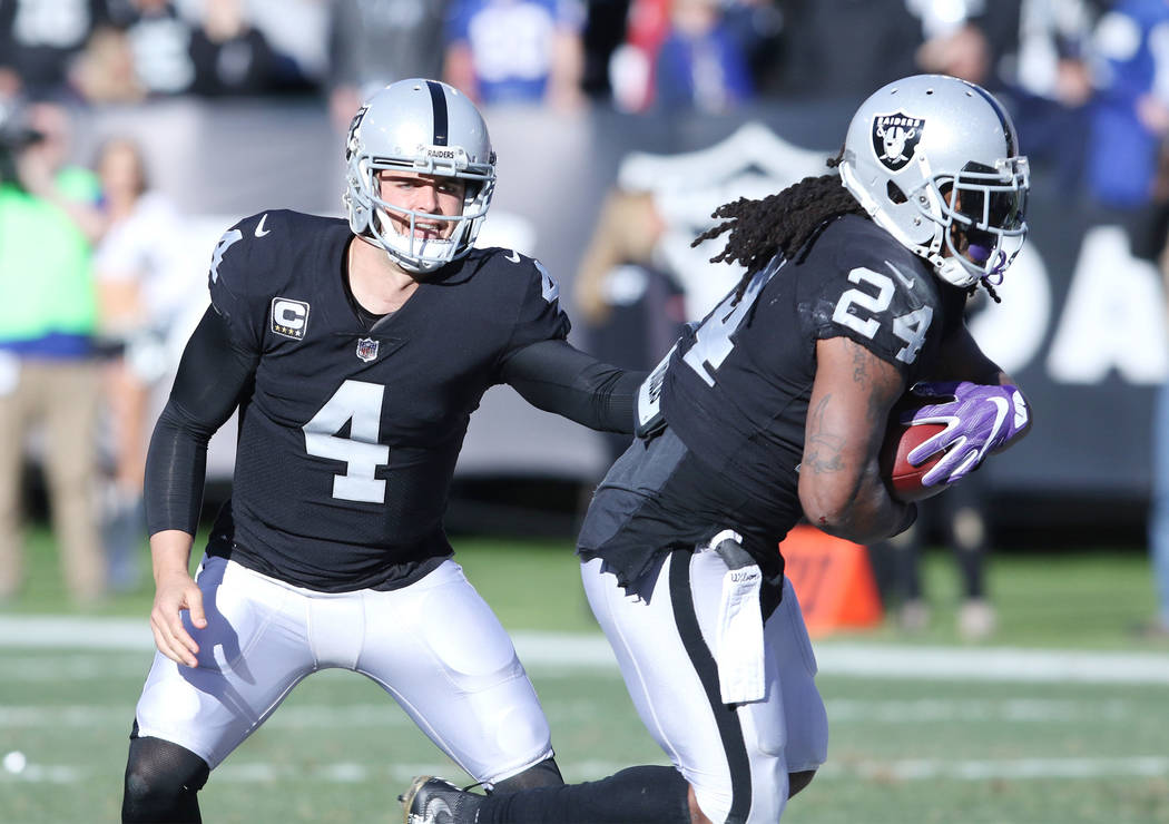 Oakland Raiders quarterback Derek Carr (4) hands off the football to running back Marshawn Lynch (24) during the first half of a NFL game against the New York Giants in Oakland, Calif., Sunday, De ...