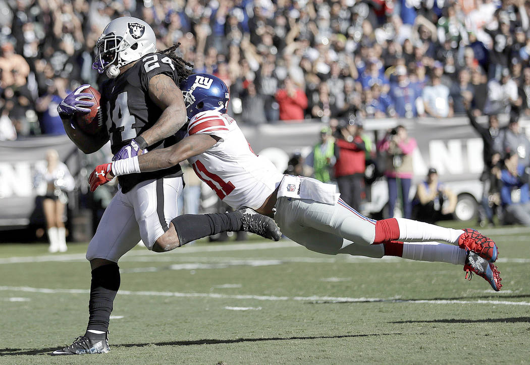 Oakland Raiders running back Marshawn Lynch (24) scores a touchdown in front of New York Giants cornerback Dominique Rodgers-Cromartie during the first half of an NFL football game in Oakland, Cal ...