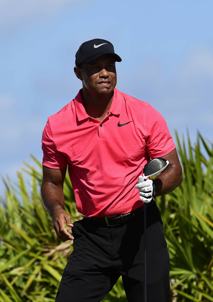Tiger Woods gestures watches his shot from the third tee during the final round of the Hero World Challenge golf tournament at Albany Golf Club in Nassau, Bahamas, Sunday, Dec. 3, 2017. (AP Photo/ ...