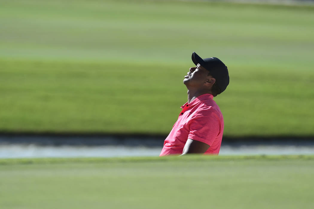 Tiger Woods reacts after a shot from a bunker on 17 during the final round of the Hero World Challenge golf tournament at Albany Golf Club in Nassau, Bahamas, Sunday, Dec. 3, 2017. (AP Photo/Dante ...
