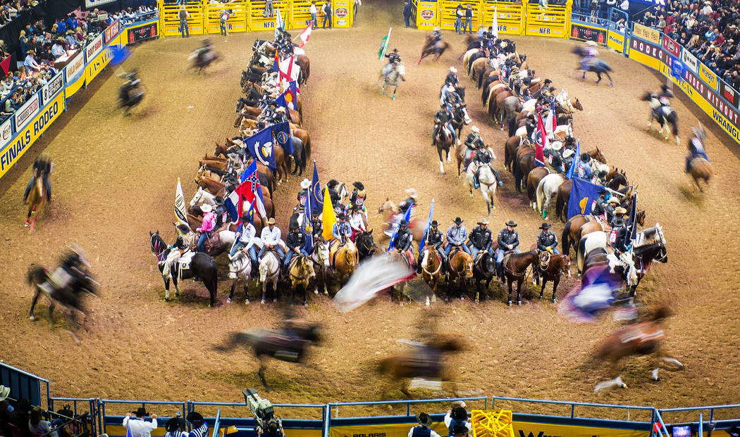 Contestants enter the arena during the opening ceremony on the first night of the National Finals Rodeo at the Thomas & Mack Center in Las Vegas on Thursday, Dec. 7, 2017. Chase Stevens Las Ve ...