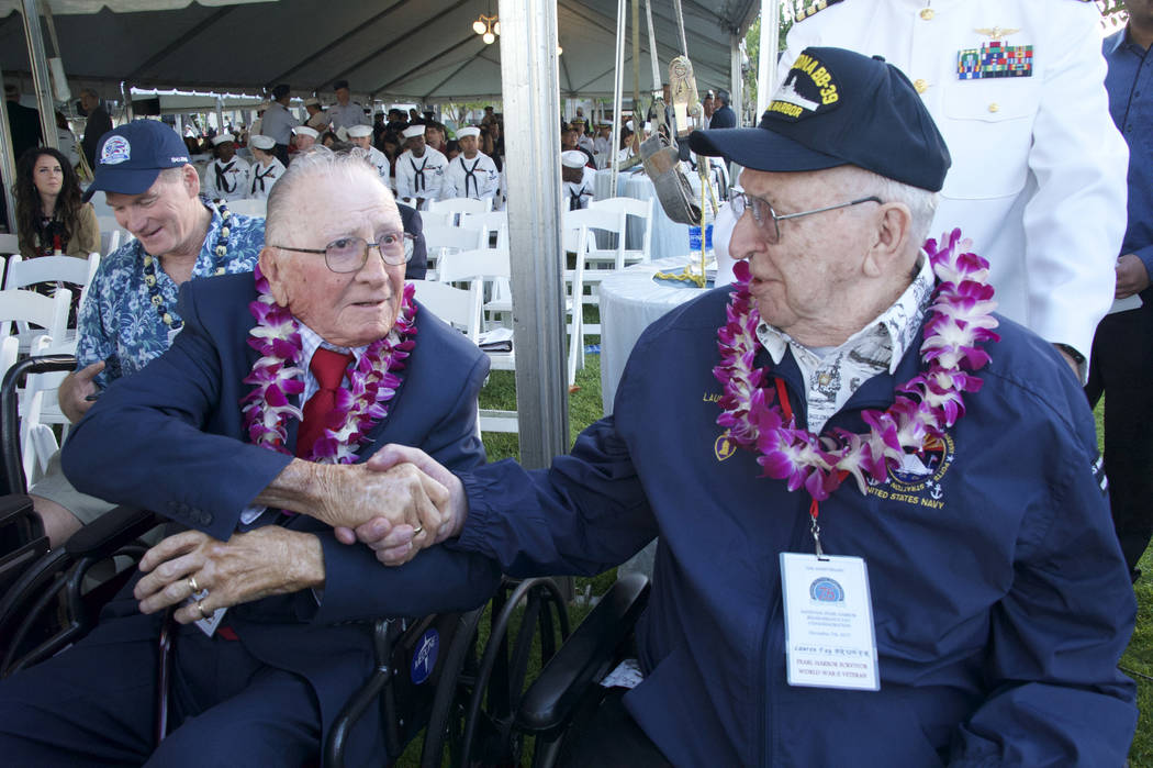 Don Stratton, left, shakes Lauren Bruner's hand after arrival at ceremonies at the Arizona Memorial in Honolulu, Hawaii., Thursday, Dec. 7, 2017.  Survivors gathered Thursday at the site of the Ja ...