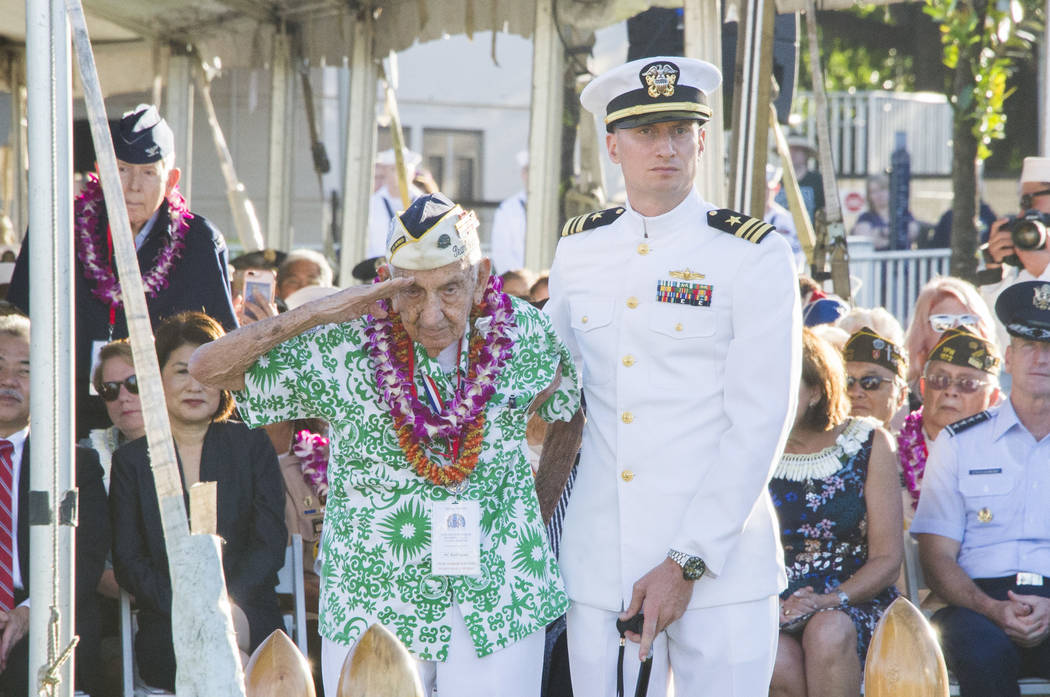 Pearl Harbor survivor, Al Rodrigues salutes for the audience during  a ceremony at the Arizona Memorial in Honolulu, Hawaii., Thursday, Dec. 7, 2017.  Survivors gathered Thursday at the site of th ...