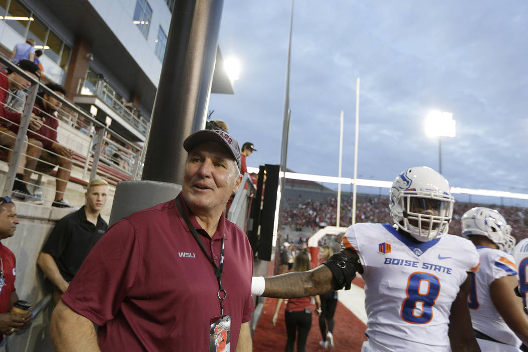 Former NFL Washington Redskins and Washington State quarterback Mark Rypien, left, stands on the field before an NCAA college football game between Washington State and Boise State in Pullman, Was ...