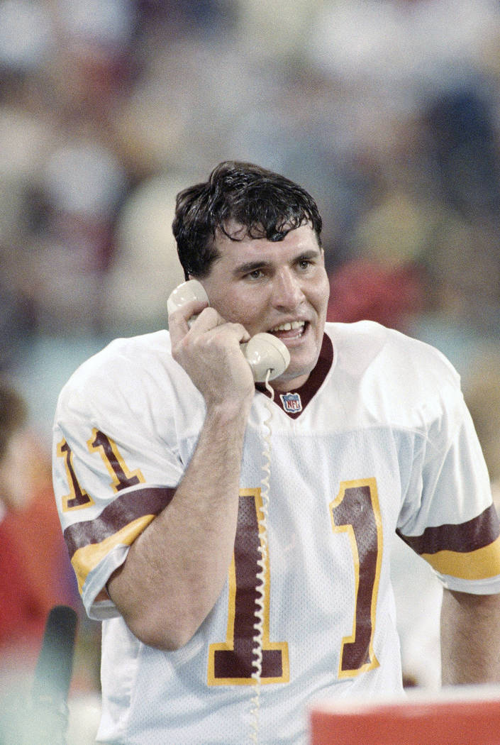 Washington Redskins quarterback Mark Rypien talks with the coaches in the press box during the second quarter after the Redskins scored their second touchdown in Super Bowl XXVI in Minneapolis, Su ...
