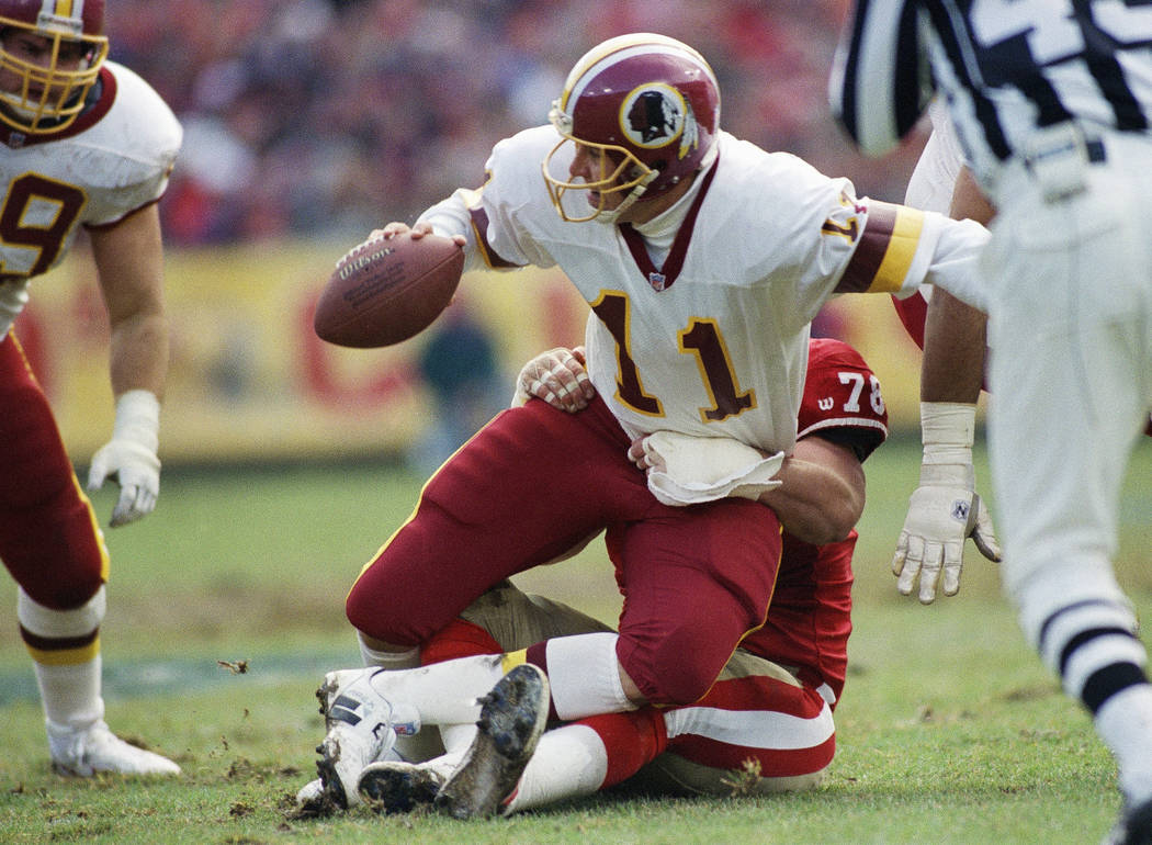 FILE - In this Jan. 9, 1993 file photo, Washington Redskins quarterback Mark Rypien (11) is sacked by San Francisco 49ers' Pierce Holt (78) during an NFL football game in San Francisco. Rypien is  ...